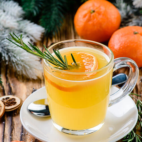 Orange winter punch with a sprig of rosemary in it