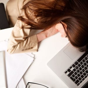 Woman asleep on her desk with laptop and paperwork in view.